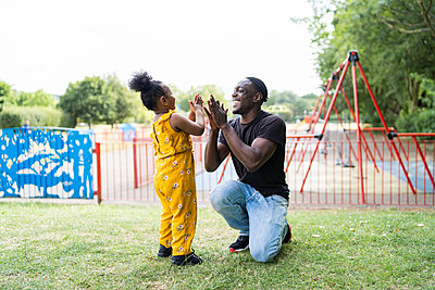 Happy father and daughter playing a clapping game in a park - p300m2154846 by Francesco Buttitta