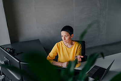 Female entrepreneur looking away while sitting at desk in office - p300m2276101 by Oxana Guryanova
