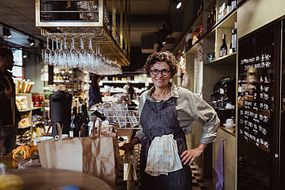 Portrait of smiling female owner with hand on hip at deli store - p426m2270483 by Maskot