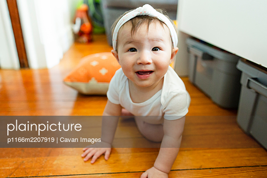 Curious baby girl makes eye contact while crawling on floor at home - p1166m2207919 by Cavan Images