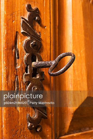 Close up of rustic antique metal escutcheon and key on wooden door. - p924m2186520 by Perry Mastrovito