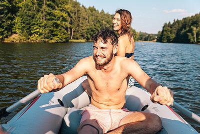 Junger Mann und junge Frau paddeln auf See - p1358m1214711 von Nolting