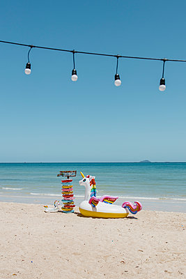 Unicorn and colourful floatation devices on the beach - p728m2288129 by Peter Nitsch