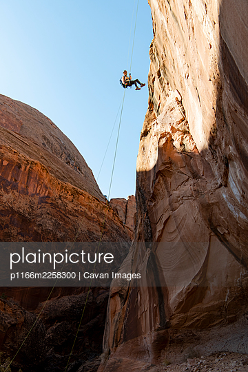 Low angle view of young woman canyoneering on mountain - p1166m2258300 by Cavan Images