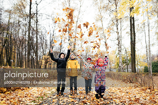 Group of four kids playing with autumn leaves - p300m2140299 by Ekaterina Yakunina
