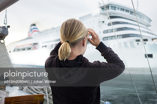 Woman looking at cruise ship - p312m2080461 by Johan Willner