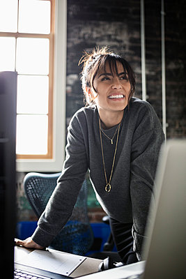 Smiling, confident creative businesswoman in office - p1192m2040585 by Hero Images