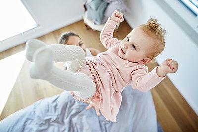 Mutter wirft Baby hoch in die Luft - p1359m1221637 von Great Images