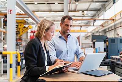 Female entrepreneur with book while male colleague working on laptop in factory - p300m2240135 by Daniel Ingold