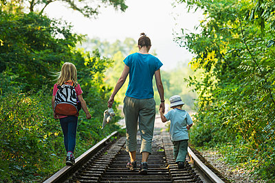Mother with boy and girl walking along abandoned railway track, near Clecy; Normandy, France - p442m967690 by Ian Cumming