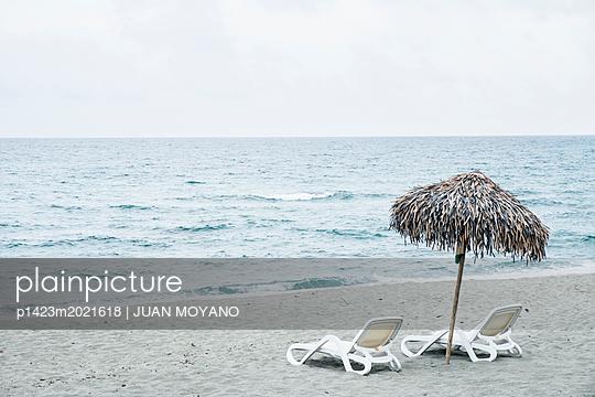 Zwei Sonnenliegen und Sonnenschirm am Strand - p1423m2021618 von JUAN MOYANO