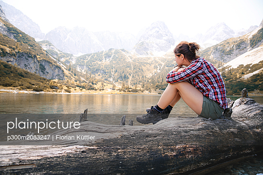 Austria, Tyrol, woman sitting on tree trunk at lake Seebensee - p300m2083247 by Florian Küttler