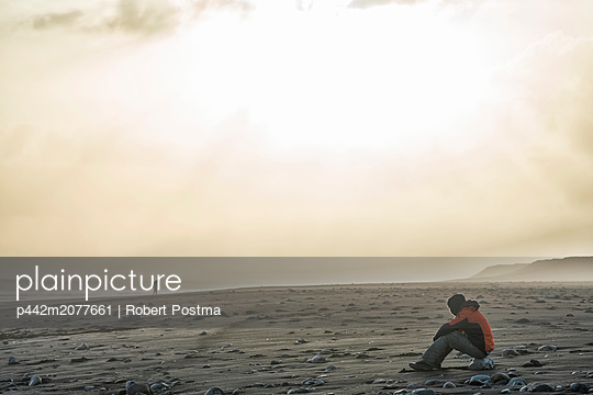 Person sitting on the shore of Southern Iceland while watching another person walking in the distance. Moody lighting illuminates the landscape; Iceland - p442m2077661 by Robert Postma