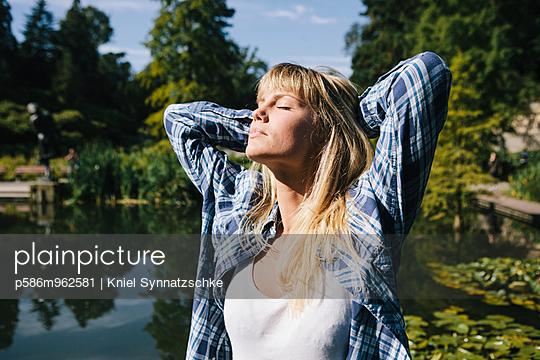 Junge Frau mit blonden Haaren im Sonnenschein - p586m962581 von Kniel Synnatzschke