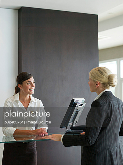 A businesswoman and a receptionist - p9248976f by Image Source
