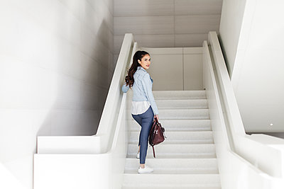 Back view of young lady with message bag by white staircase - p1166m2095875 by Cavan Images