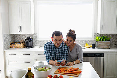 Couple using smart phone, preparing dinner in kitchen - p1192m2088639 by Hero Images