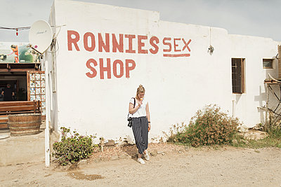 Young woman in front of sex shop in South Africa - p1477m1586666 by rainandsalt