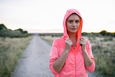 Mid adult woman holding hooded jacket at country road - p300m2273514 by Andrés Benitez