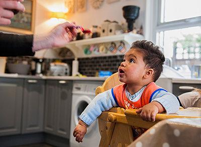 Baby boy in highchair being fed - p429m1469381 by G. Mazzarini