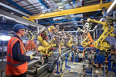 Apprentice engineer programming robots in car factory - p429m2138390 by Monty Rakusen