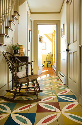 Hallway in colonial home with colorful wooden floor - p5551690f by Darren Setlow