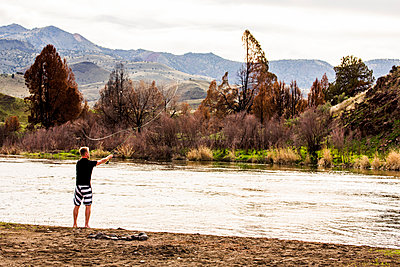 Caucasian man fishing in remote river, Painted Hills, Oregon, United States - p555m1412149 by Adam Hester