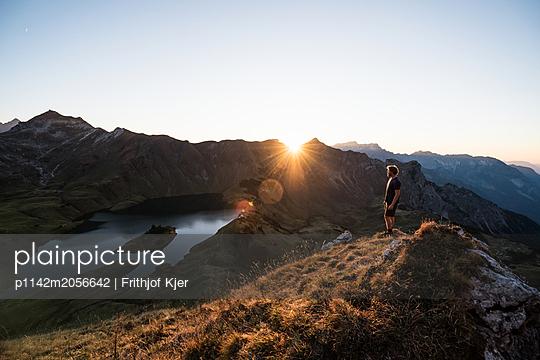 Junger Mann genießt Sonnenuntergang in den bergen  - p1142m2056642 von Runar Lind