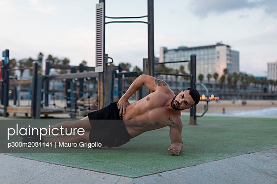 Barechested muscular man doing side planks outdoors - p300m2081141 by Mauro Grigollo