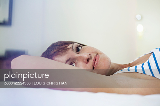 Contemplating woman looking away while lying down in bedroom at home - p300m2224953 by LOUIS CHRISTIAN