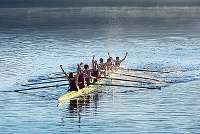 Rowing team celebrating in scull on lake - p1023m923679f by Chris Ryan