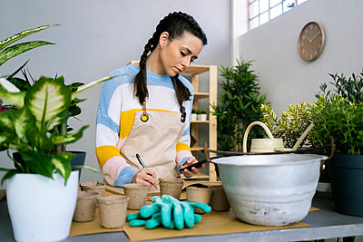 Young woman working in a gardening laboratory or plant shop - p300m2275349 von Giorgio Fochesato