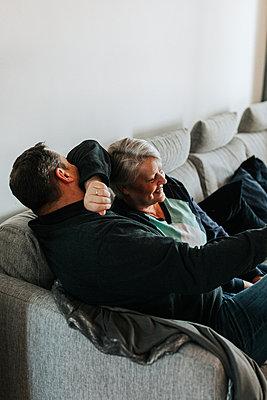 Mature couple sitting on sofa - p312m2191030 by Jennifer Nilsson