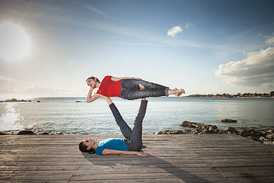 Women practising acro yoga at seaside - p429m2090650 by ROBERTO PERI