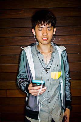 Asian man listening to music with cell phone - p555m1411627 by Adam Hester