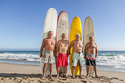 Older men holding surfboards on beach - p555m1413812 by Studio Zanello/Circlestock Images