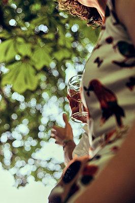 Frau mit Weinglas im Garten - p900m1475075 von Michael Moser