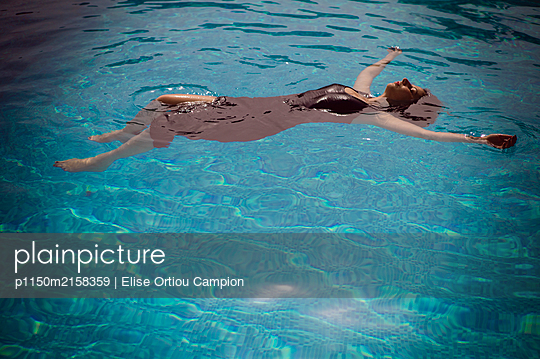 Bekleidete Frau im Swimmingpool - p1150m2158359 von Elise Ortiou Campion