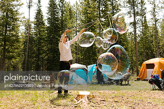 Man making large soap bubbles on camping, Wasatch-Cache National Forest - p1427m2213559 by Jessica Peterson