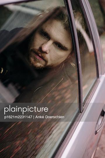 Man in a car, portrait - p1621m2231147 by Anke Doerschlen