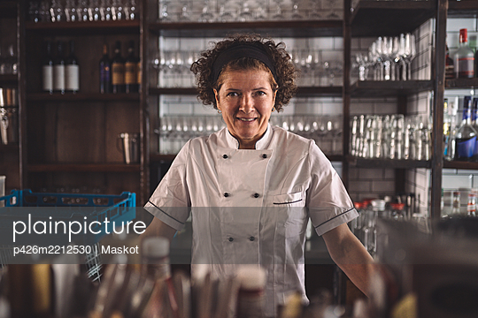 Portrait of smiling female chef in commercial kitchen - p426m2212530 by Maskot