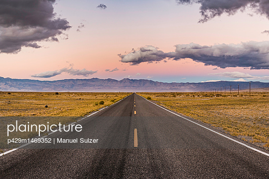 Straight road at sunset in Death Valley National Park, California, USA - p429m1469352 by Manuel Sulzer