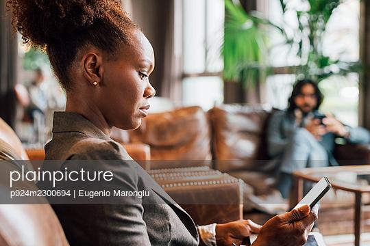Italy, Profile of businesswoman with smart phone in creative studio - p924m2300694 by Eugenio Marongiu
