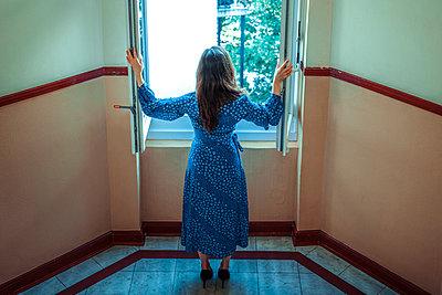 Frau steht am Fenster  - p045m2014781 von Jasmin Sander