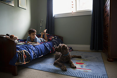 Boy with book bed looking at dog floor - p1192m1078230f by Hero Images