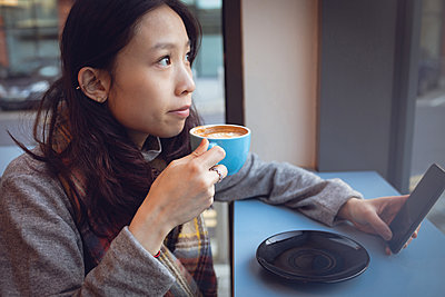 Thoughtful woman having coffee at table in cafeteria - p1315m1566100 by Wavebreak