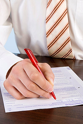 Businessman filling in application form, close-up, mid section - p3006770f by Westend61