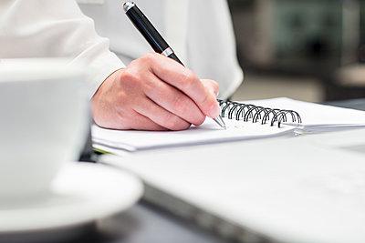 Woman making notes in diary - p300m1581192 von zerocreatives