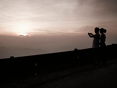 A couple stoped on a road's side photograph the landscape at sunset. Cao Bang province, Vietnam, Asia. - p934m892926 by Boris Zuliani