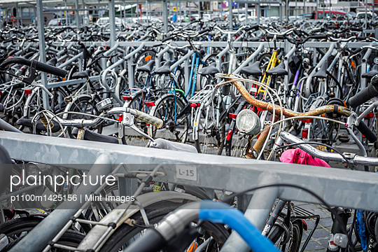 Bicycles fixed to a large urban bike rack.